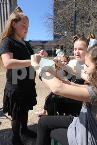 Children play with homemade slime product sold by vendor at the Coffee and Donuts Festival, Downtown Square.