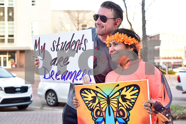 """Dan Crawford and Dalila Reynoso hold signs during a """"Migration is Beautiful"""" event at T.B. Butler Fountain Plaza in Tyler, Texas, on Tuesday, March 6, 2018. The event, themed around the migrant monarch butterfly, was in support of Dreamers and other immigrants. (Chelsea Purgahn/Tyler Morning Telegraph)"""