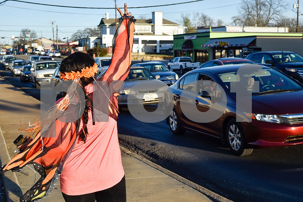 """Dalila Reynoso waves at cars during a """"Migration is Beautiful"""" event in downtown Tyler, Texas, on Tuesday, March 6, 2018. The event, themed around the migrant monarch butterfly, was in support of Dreamers and other immigrants. (Chelsea Purgahn/Tyler Morning Telegraph)"""