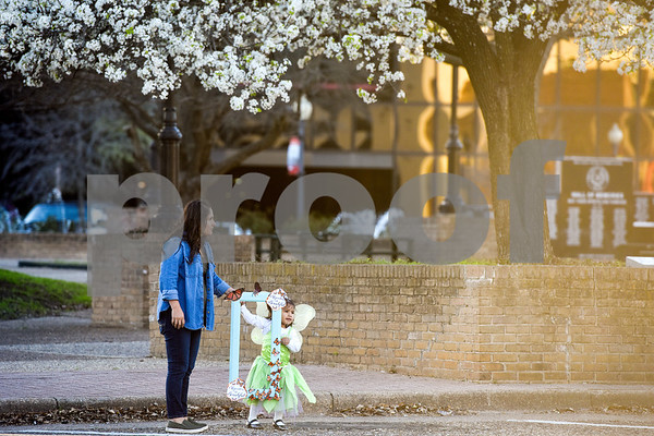 """Elsa Cruz holds Tori Morales', 2, hand as they both hold a frame during a """"Migration is Beautiful"""" event at T.B. Butler Fountain Plaza in Tyler, Texas, on Tuesday, March 6, 2018. The event, themed around the migrant monarch butterfly, was in support of Dreamers and other immigrants. (Chelsea Purgahn/Tyler Morning Telegraph)"""