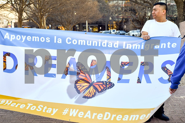 """Andres Ruiz stands behind a banner during a """"Migration is Beautiful"""" event at T.B. Butler Fountain Plaza in Tyler, Texas, on Tuesday, March 6, 2018. The event, themed around the migrant monarch butterfly, was in support of Dreamers and other immigrants. (Chelsea Purgahn/Tyler Morning Telegraph)"""