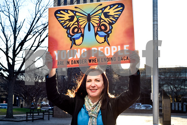 """Kristin Stephens holds a sign during a """"Migration is Beautiful"""" event at T.B. Butler Fountain Plaza in Tyler, Texas, on Tuesday, March 6, 2018. The event, themed around the migrant monarch butterfly, was in support of Dreamers and other immigrants. (Chelsea Purgahn/Tyler Morning Telegraph)"""