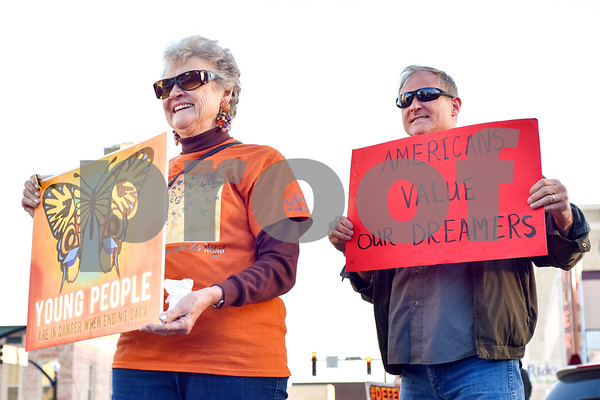 """Shirley Walston and Dustin Stephens hold signs during a """"Migration is Beautiful"""" event at T.B. Butler Fountain Plaza in Tyler, Texas, on Tuesday, March 6, 2018. The event, themed around the migrant monarch butterfly, was in support of Dreamers and other immigrants. (Chelsea Purgahn/Tyler Morning Telegraph)"""
