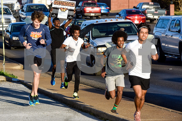 """Jack Gipson, Simon Gachibi, Haftu Knight, Nick Knight and Cesar Correa run during a """"Migration is Beautiful"""" event in downtown Tyler, Texas, on Tuesday, March 6, 2018. The event, themed around the migrant monarch butterfly, was in support of Dreamers and other immigrants. (Chelsea Purgahn/Tyler Morning Telegraph)"""