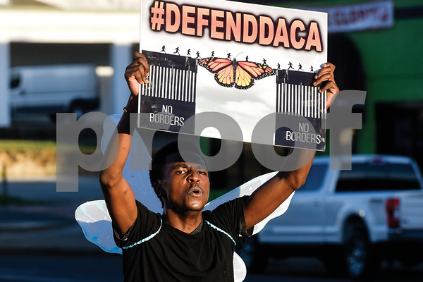 """Simon Gachibi runs with a sign during a """"Migration is Beautiful"""" event at T.B. Butler Fountain Plaza in Tyler, Texas, on Tuesday, March 6, 2018. The event, themed around the migrant monarch butterfly, was in support of Dreamers and other immigrants. (Chelsea Purgahn/Tyler Morning Telegraph)"""