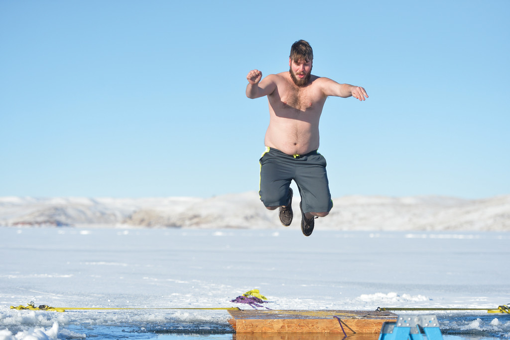 Ashleigh Fox | The Sheridan Press<br /> Ryan Carter of Sheridan leaps off the deck into the Polar Plunge hole in Lake DeSmet Jan. 1, 2018. Carter, now 24, completed his first of two Polar Plunges at 16 years old.