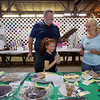 Judging and setup at the static exhibits building ahead of Friday's opening day of the Middlesex County 4-H Fair. Co-chairs of Food Amy Herrick of Billerica, left, and her son Chris Herrick of Mansfield, lay out the food entries and ribbons, with help from Chris' daughter Katelynn Herrick, 7. (SUN/Julia Malakie)