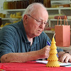 Judging and setup at the static exhibits building ahead of Friday's opening day of the Middlesex County 4-H Fair. Gerry Boyle of Concord judges the beeswax entries. He judges beeswax, honey and maple products. (SUN/Julia Malakie)