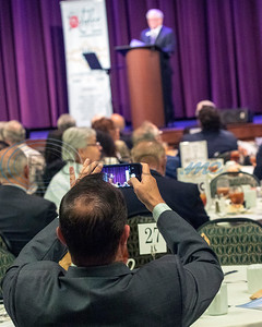 An attendee at the 30th Annual TEDC Investors and Contributors Appreciation Luncheon, held on April 11, 2019 at the Crosswalk Convention Center, Tyler, TX, records TEDC President/CEO Tom Mullins as he presents  the President's 2018 Activity Report. (Rick Flack/Freelance)
