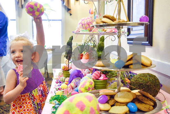 Lyla Richey, 4, holds up a colorful egg during a community Easter party at The Hamptons in Tyler, Texas, on Friday, April 14, 2017. The event included live music, snow cones and other snacks, and an Easter egg hunt for children. (Chelsea Purgahn/Tyler Morning Telegraph)