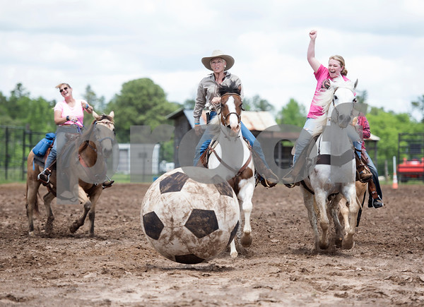 Brenda Jones of Maydelle and Brittany Ranes of Jacksonville race their horses toward a large rubber soccer ball as they play mounted soccer Tuesday during the 1836 Chuckwagon Race in Neches. The western culture event continues through Sunday.   (Sarah A. Miller/Tyler Morning Telegraph)