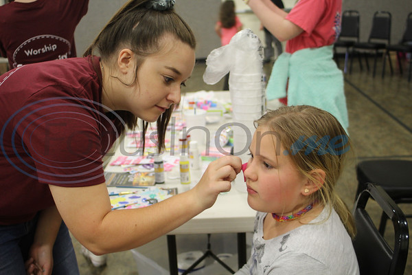 Kaycee Griffith paints Kallie Dockters face at the Easter Eggstavaganza at First Baptist Church in Bullard. Sarah Perez/Freelance