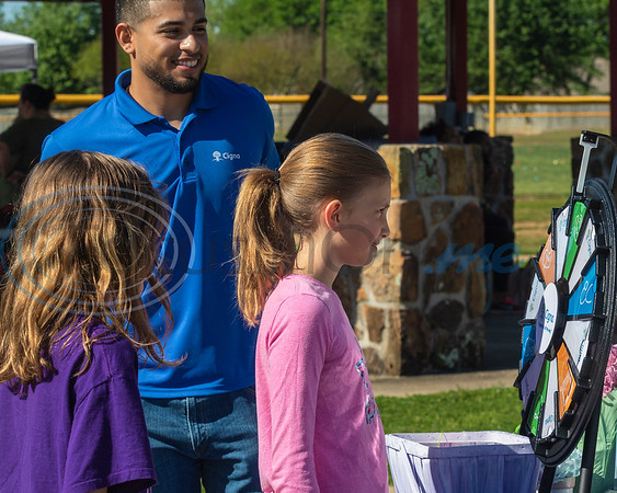 Chris McFarland, of Cigna HealthSpring (C) , looks on as Sebastian Walborn (R) and Fiona Walborn (L) spin the wheel at the 4th Annual Community of Whitehouse Easter Egg Hunt, Saturday,  April  20th,  at the Whitehouse Sports Complex in Tyler, Tx. (Rick Flack/Freelance)