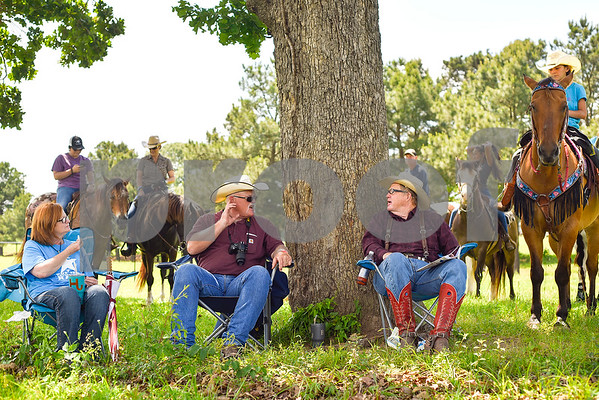 Tammy and Ronnie Jenkins chat with Phil Runge in the shade during the fifth annual 1836 Chuckwagon Race presented by Diamond Ranch in Neches, Texas, on Friday, April 21, 2017. Hundreds came to the event to see cattle roping, horse racing, live music and more. (Chelsea Purgahn/Tyler Morning Telegraph)
