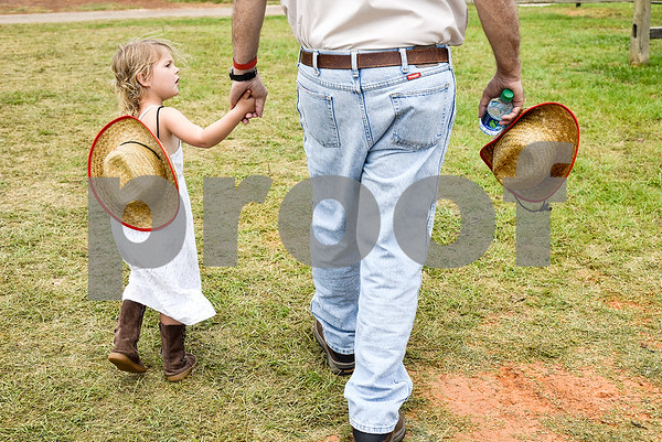 Alice Wall, 3, holds her grandfather Johnny McCurry's hand as they walk to the arena during the fifth annual 1836 Chuckwagon Race presented by Diamond Ranch in Neches, Texas, on Friday, April 21, 2017. Hundreds came to the event to see cattle roping, horse racing, live music and more. (Chelsea Purgahn/Tyler Morning Telegraph)
