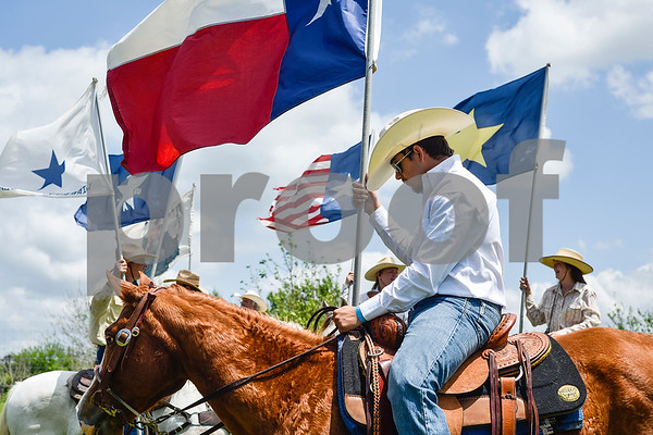 Jake Williams holds a Texas flag during the fifth annual 1836 Chuckwagon Race presented by Diamond Ranch in Neches, Texas, on Friday, April 21, 2017. Hundreds came to the event to see cattle roping, horse racing, live music and more. (Chelsea Purgahn/Tyler Morning Telegraph)