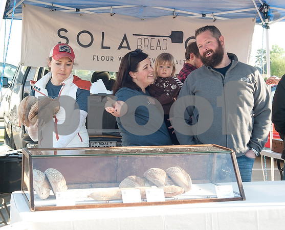 Lindsay Long, Karin Davis, Penelope Davis, 1, and Blaine Davis work at the Sola Bread booth at the Rose City Farmers Market held in the parking lot of Juls Saturday April 2, 2016.  (Sarah A. Miller/Tyler Morning Telegraph)