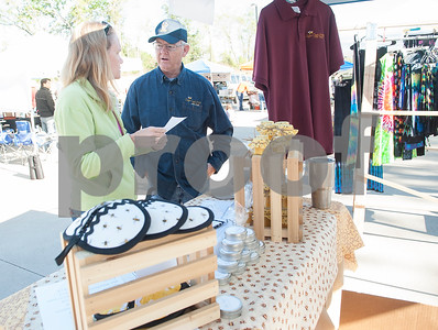 Jenifer Hendrix talks with Sugar Creek Honey owner Jim Biles at the Rose City Farmers Market held in the parking lot of Juls Saturday April 2, 2016.  (Sarah A. Miller/Tyler Morning Telegraph)