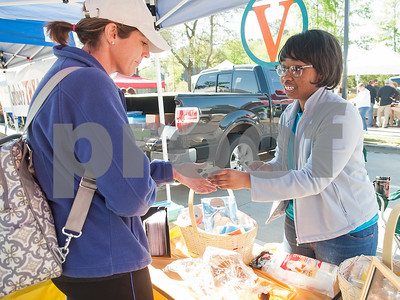 Kerrigan Sanders of Sugar Boogah Confections, right, hands Nan Robinson a sample of her allergy-free baked goods at the Rose City Farmers Market held in the parking lot of Juls Saturday April 2, 2016.  (Sarah A. Miller/Tyler Morning Telegraph)
