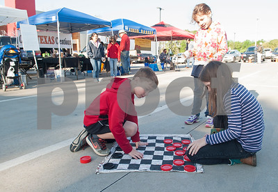 Annabelle Davis, 6, watches Christopher Johnson, 7, and Melissa Grubb, 10, play checkers at the Rose City Farmers Market held in the parking lot of Juls Saturday April 2, 2016.  (Sarah A. Miller/Tyler Morning Telegraph)