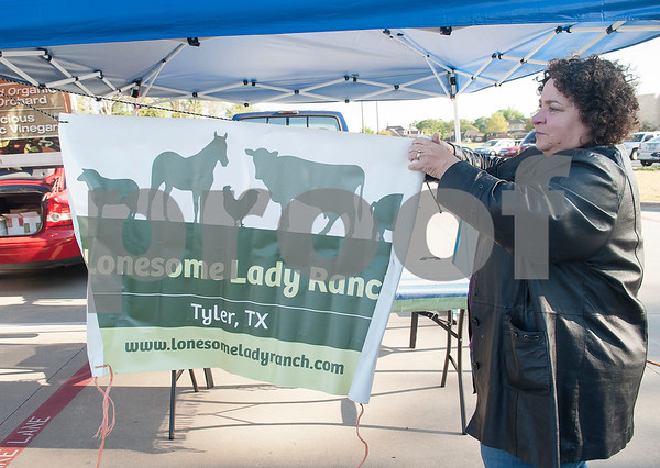 Bonnie Grub hangs a sign for Lonesome Lady Ranch at the Rose City Farmers Market held in the parking lot of Juls Saturday April 2, 2016.  (Sarah A. Miller/Tyler Morning Telegraph)