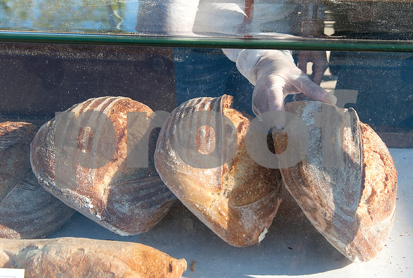 Lindsay Long sets out new loaves of bread at the Sola Bread booth at the Rose City Farmers Market held in the parking lot of Juls Saturday April 2, 2016.  (Sarah A. Miller/Tyler Morning Telegraph)