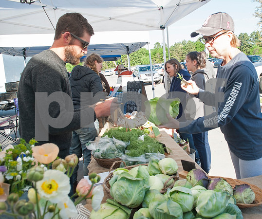 Nancy Hart buys a cabbage from Red Moon Farm owner Justin Bullock at the Rose City Farmers Market held in the parking lot of Juls Saturday April 2, 2016.  (Sarah A. Miller/Tyler Morning Telegraph)