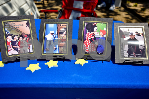 Photographs sit on display at the Make-A-Wish Foundation booth during East Texas Giving Day at T.B. Butler Fountain Plaza in Tyler, Texas, on Tuesday, April 25, 2017. East Texas Giving Day is designed to make the most of social media by getting donors to share the fact that they made a donation with their friends and followers on social media. The hope is for those shares to inspire interest and potentially more donations. (Chelsea Purgahn/Tyler Morning Telegraph)