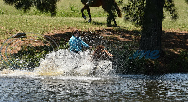 A rider races across a pond during the Alamo Horse Race as part of the 1836 Chuckwagon Races events at Diamond B Ranch. The race took place on Saturday, April 27 with winning riders advancing to the finals on Sunday. (Jessica T. Payne/Tyler Morning Telegraph)
