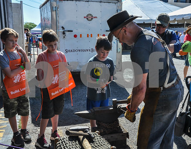 """Tucker Ponder, 8, makes a blade with the help of blacksmith Charles Adams of Shadowhawk Blades at the 6th Annual Tyler Maker Faire at The Science Discovery Place on Saturday, April 28. The event featured more than 45 """"makers"""" and their inventions. (Jessica T. Payne/Tyler Paper)"""