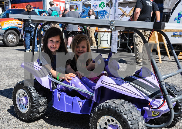 Lizzie Ravanesi, 6, (left) and Sophie Ravanesi, 4, (right) take a test drive in a solar-paneled kids car at the 6th Annual Tyler Maker Faire. The event took place on Saturday, April 28 at The Science Discovery Place. (Jessica T. Payne/Tyler Paper)