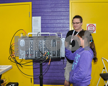 Hazel Lively, 10, tries out a music synthesizer machine with the help of Garret Klein with synthesizers.com at the 6th Annual Tyler Maker Faire on Saturday, April 28. The event, which draws more than 1,200 people, took place at The Discovery Science Place in Tyler. (Jessica T. Payne/Tyler Paper)