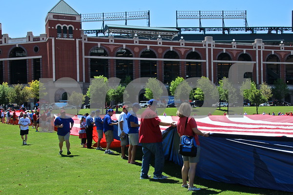 Stretching the flag taught outside Globe Life Park by james bauer