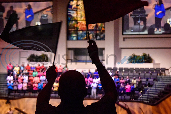 A man waves flags in worship during the re:new Gathering ahead of CityFest East Texas, which will be held in October, at Green Acres Baptist Church in Tyler, Texas, on Thursday, April 4, 2019. (Chelsea Purgahn/Tyler Morning Telegraph)