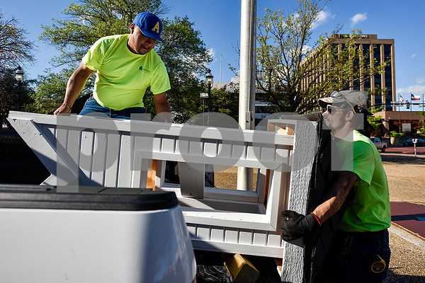 Jorge Soto and Joshua Timms take a steeple for a church playhouse out of a truck bed as the move the playhouse to T.B. Butler Fountain Plaza in Tyler, Texas, on Thursday, March 30, 2017. Eight playhouses were built and donated for Playhouses on the Plaza, a live auction benefiting the Habitat for Humanity of Smith County. (Chelsea Purgahn/Tyler Morning Telegraph)