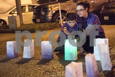 Sarah McPherson and her son Connor Dickens, 8, light a luminary to honor McPherson's father Tommy McPherson during Relay for Life of Smith County at the T.B. Butler Fountain Plaza Friday night April 8, 2016. Tommy McPherson is battling esophageal cancer.  (Sarah A. Miller/Tyler Morning Telegraph)