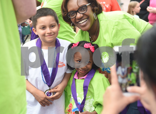 Cancer survivor Christian Arroyo, 12, of Tyler, takes a photograph with Dr. Katrina Glover and her daughter Jillian Glover, 4, during Relay for Life of Smith County at the T.B. Butler Fountain Plaza Friday night April 8, 2016.  (Sarah A. Miller/Tyler Morning Telegraph)