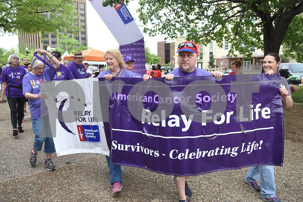 Cancer survivors carry a banner at the start of the survivor's lap during Relay for Life of Smith County at the T.B. Butler Fountain Plaza Friday night April 8, 2016.  (Sarah A. Miller/Tyler Morning Telegraph)