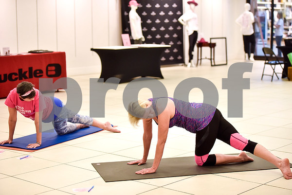 People practice yoga during a Project: OM yoga class at Broadway Square Mall in Tyler, Texas, on Friday, May 12, 2017. Manduka, a yoga mat and accessory brand, hosted Project: OM, the world's largest yoga class across the country, with 100 percent of event donations benefiting the Susan G. Komen. (Chelsea Purgahn/Tyler Morning Telegraph)