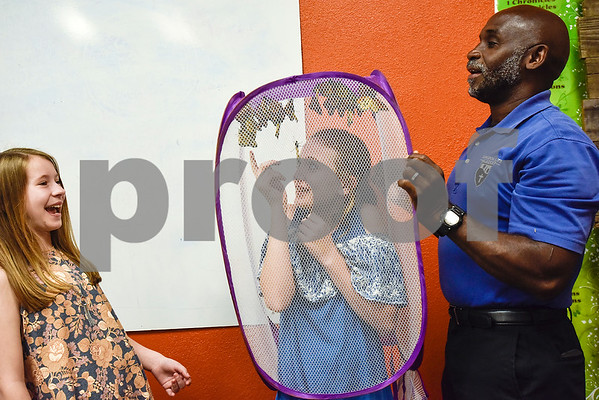 Hadassah Chapman, 10, laughs as Michalah Garrett, 12, tries to touch a monarch butterfly while Joel Enge holds a mesh laundry basket full of monarch butterflies over her head at Colonial Hills Baptist Church in Tyler, Texas, on Sunday, May 14, 2017. Enge has been raising butterflies as a hobby for 16 years and typically does a butterfly release each year with either his students or his church. (Chelsea Purgahn/Tyler Morning Telegraph)