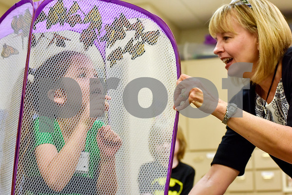 Leslie White holds a mesh laundry basket full of monarch butterflies over Rachel Rocco's, 6, head at Colonial Hills Baptist Church in Tyler, Texas, on Sunday, May 14, 2017. Joel Enge has been raising butterflies as a hobby for 16 years and typically does a butterfly release each year with either his students or his church. (Chelsea Purgahn/Tyler Morning Telegraph)