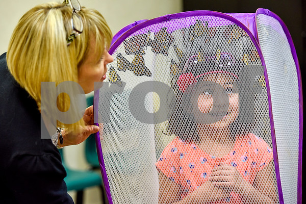 Leslie White holds a mesh laundry basket full of monarch butterflies over Leilani Estrella's head at Colonial Hills Baptist Church in Tyler, Texas, on Sunday, May 14, 2017. Joel Enge has been raising butterflies as a hobby for 16 years and typically does a butterfly release each year with either his students or his church. (Chelsea Purgahn/Tyler Morning Telegraph)