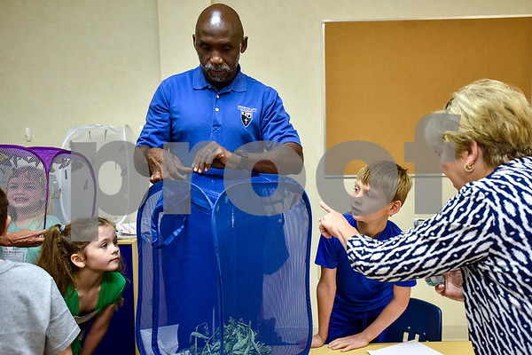 Joel Enge, center, unzips a mesh laundry basket to show kindergarten Sunday school students a monarch chrysalis at Colonial Hills Baptist Church in Tyler, Texas, on Sunday, May 14, 2017. Enge has been raising butterflies as a hobby for 16 years and typically does a butterfly release each year with either his students or his church. (Chelsea Purgahn/Tyler Morning Telegraph)