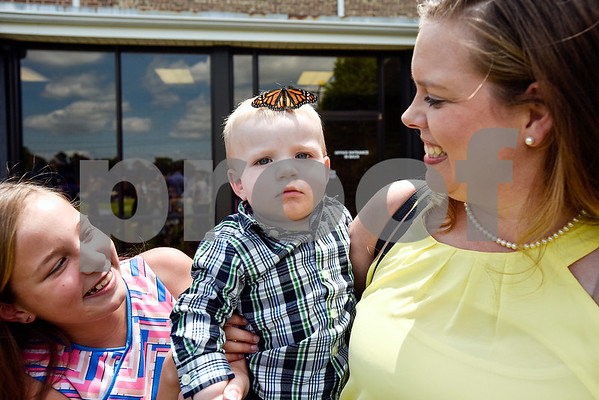 Kalynn Lloyd, 10, Andrew Lloyd, 1, and Julie Lloyd smile as a monarch butterfly sits on Andrew's head during a butterfly release at Colonial Hills Baptist Church in Tyler, Texas, on Sunday, May 14, 2017. Joel Enge has been raising butterflies as a hobby for 16 years and typically does a butterfly release each year with either his students or his church. (Chelsea Purgahn/Tyler Morning Telegraph)