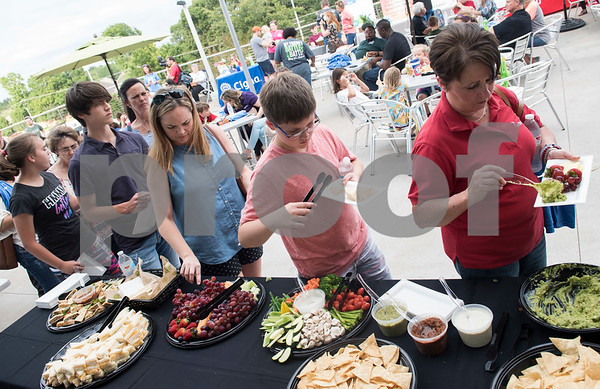 People get plates of healthy snacks to eat during the Fit City Tyler Celebration Event held at Fresh Tuesday May 16, 2017.  (Sarah A. Miller/Tyler Morning Telegraph)