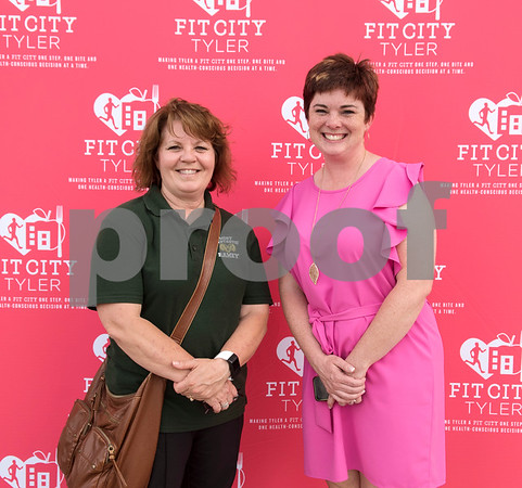 Tracy Berg of Ramey Elementary and Katy Lee of Caldwell Elementary accept their school's awards in the kids' marathon challenge winners category of the Lighten Up East Texas regional weight loss challenge over the past five years during the Fit City Tyler Celebration Event held at Fresh Tuesday May 16, 2017.  (Sarah A. Miller/Tyler Morning Telegraph)