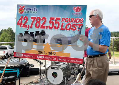 George Roberts holds a sign showing the total weight loss from competitors in the Lighten Up East Texas regional weight loss challenge over the past five years during the Fit City Tyler Celebration Event held at Fresh Tuesday May 16, 2017.  (Sarah A. Miller/Tyler Morning Telegraph)