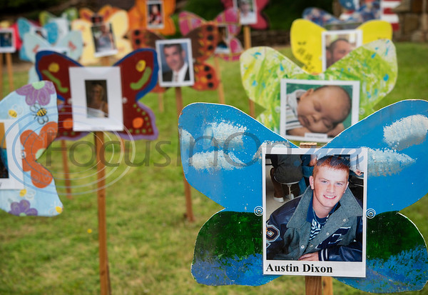 Butterfly signs paired with photos of children who have died line a grassy area at The Children's Park in Tyler for the annual Tyler Compassionate Friends butterfly release. The event recognizes children who have died and is attended by parents, siblings and other family members.  (Sarah A. Miller/Tyler Morning Telegraph)