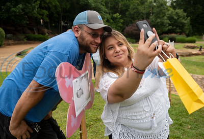 Asa and Ruby Buchanan of Tyler take a photo with the butterfly sign recognizing their daughter at The Tyler Compassionate Friends butterfly release at The Children's Park in Tyler on Saturday May 18, 2019. Their daughter Evelyn Faith Buchanan died the day she was born.  (Sarah A. Miller/Tyler Morning Telegraph)
