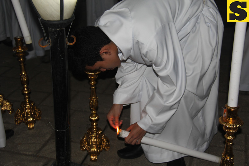 Sacristan lighting candle